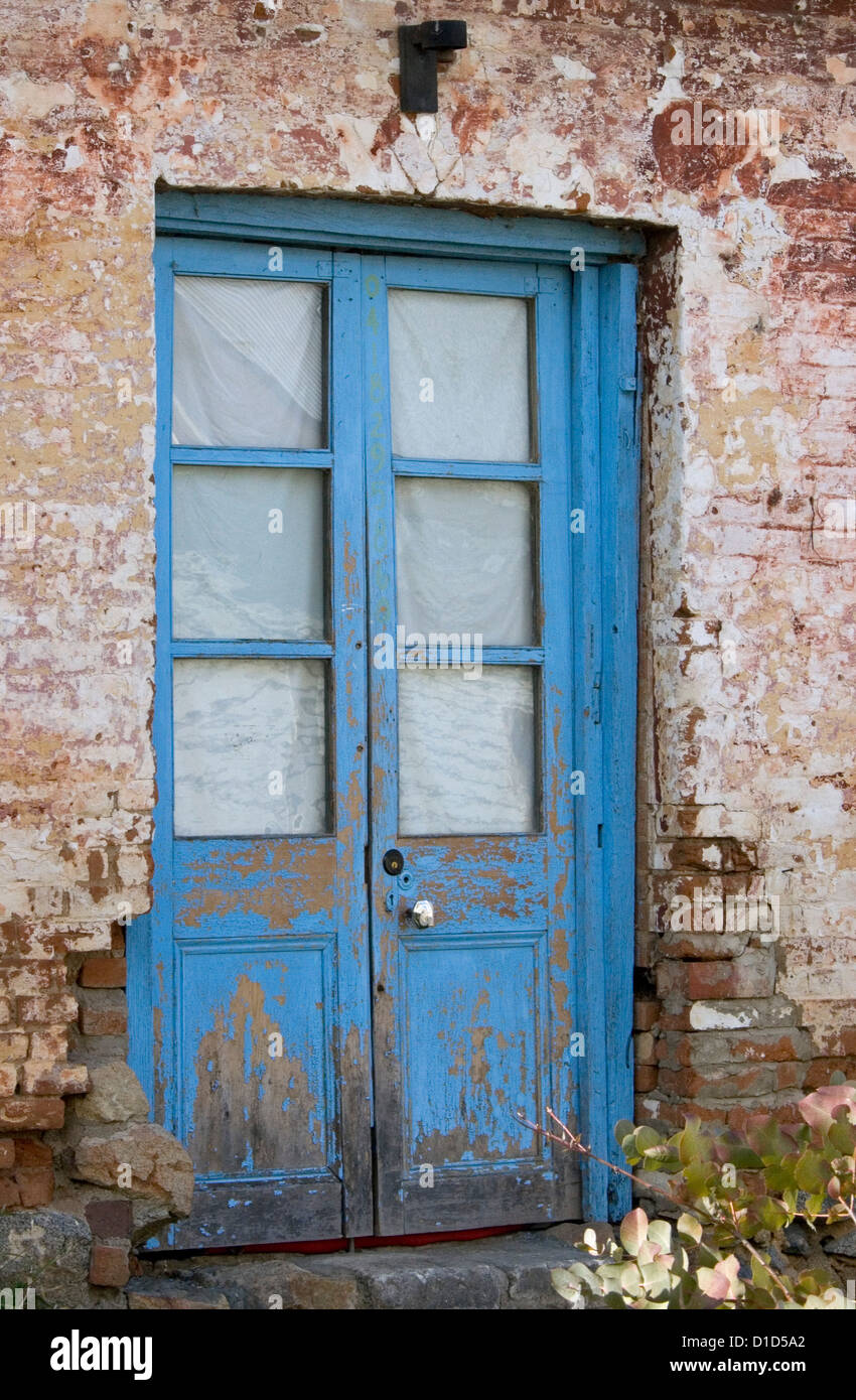 Old Blue Double Doors With Flaking Paint And Glass Panels
