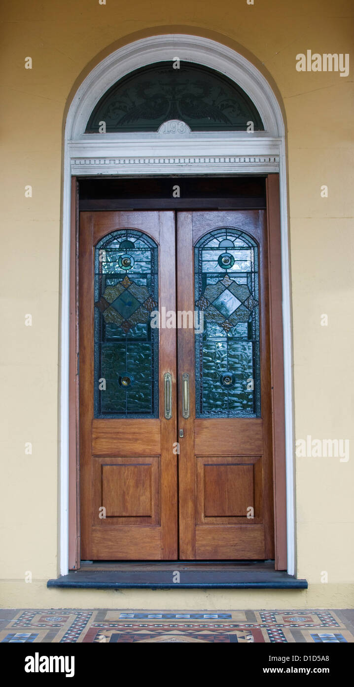 Ornate double timber doors with colourful stained glass panels and curved stained glass segment above door in cream - Stock Image