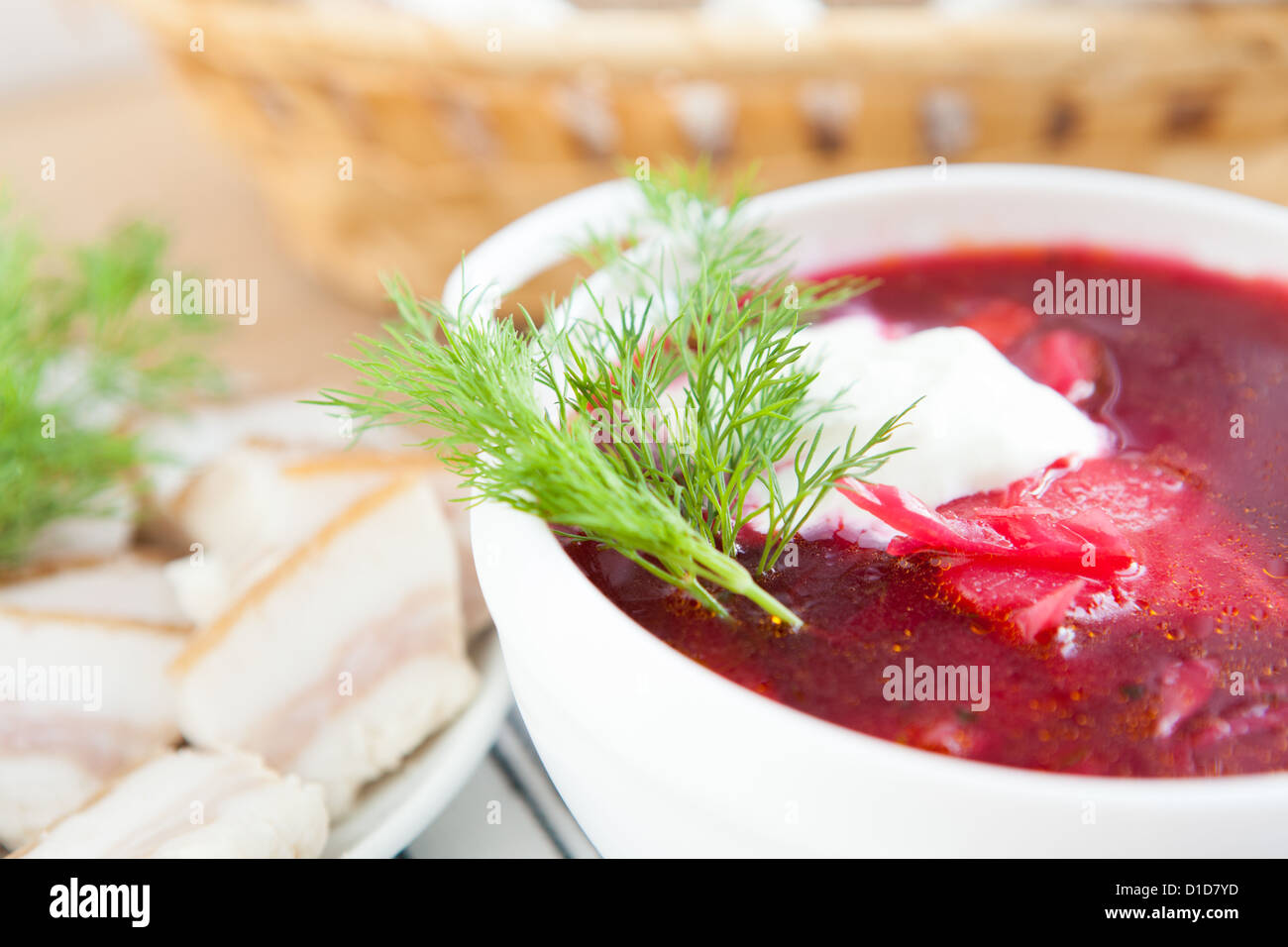 red borscht with sour cream and dill in a white tureen, close-up Stock Photo