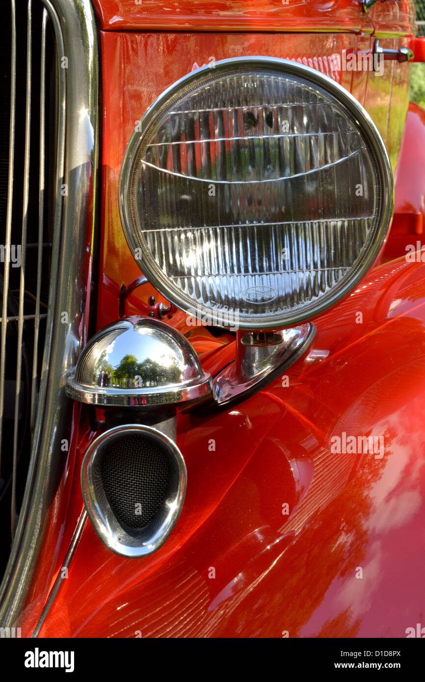 closeup shot of details of front end of red antique car, showing part of front grill and one headlamp - Stock Image