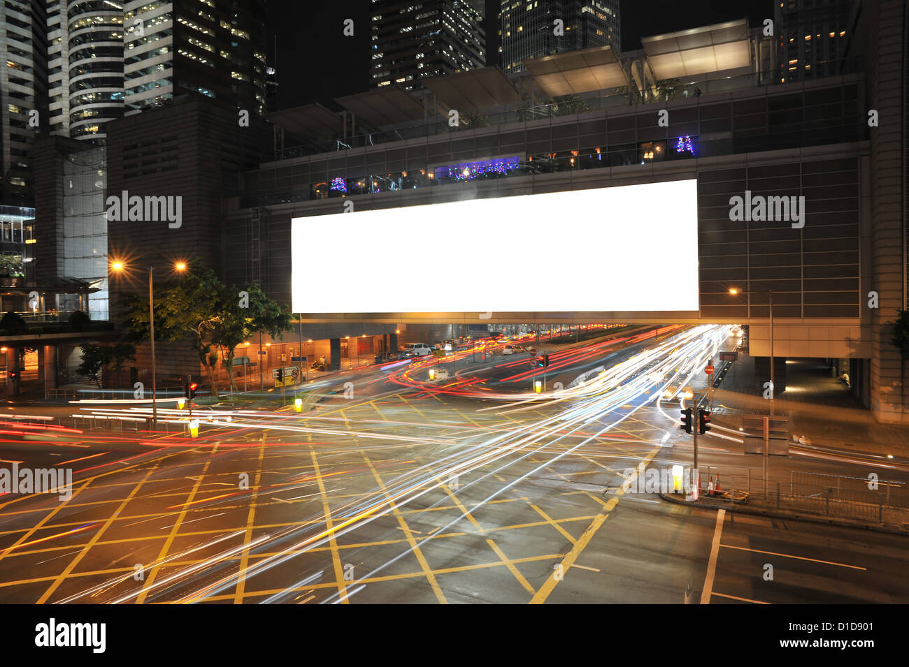 Big Empty Billboard at night in city with busy traffic - Stock Image