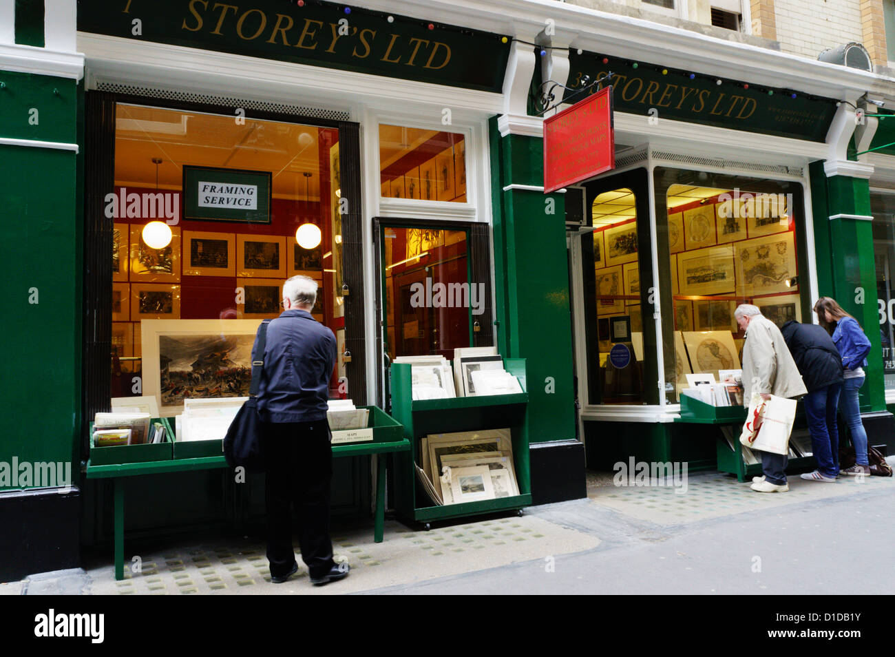 People browsing in the windows of book shops in Cecil Court in Central London. - Stock Image