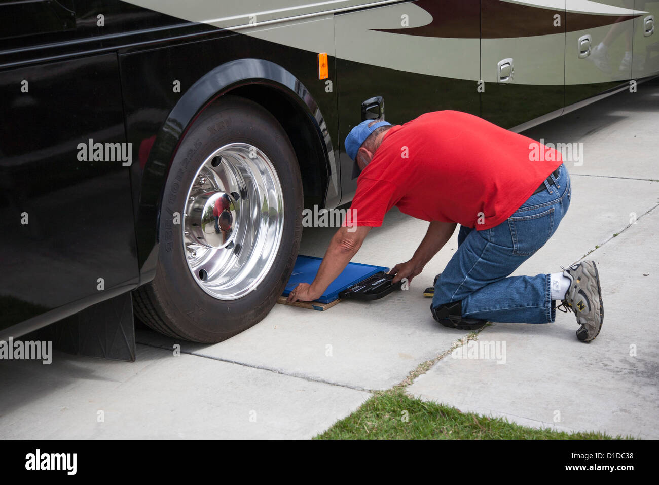 Man places portable scale in position to weigh motor coach at RV resort in Brunswick, Georgia - Stock Image