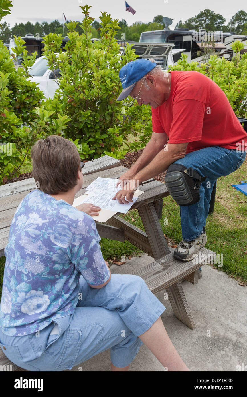 Man reviews motor coach weighing report paperwork with woman at RV resort in Brunswick, Georgia - Stock Image