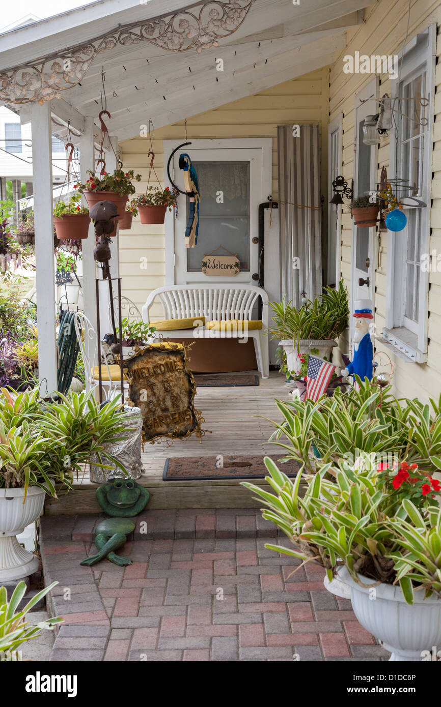 Cozy porch of older home with wooden deck and lots of potted plants - Stock Image