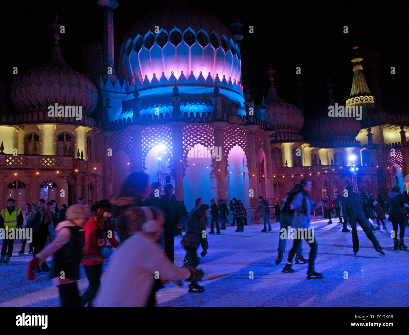 People skating in the evening on a temporary ice rink,erected in Pavilion Gardens,Brighton. - Stock Image