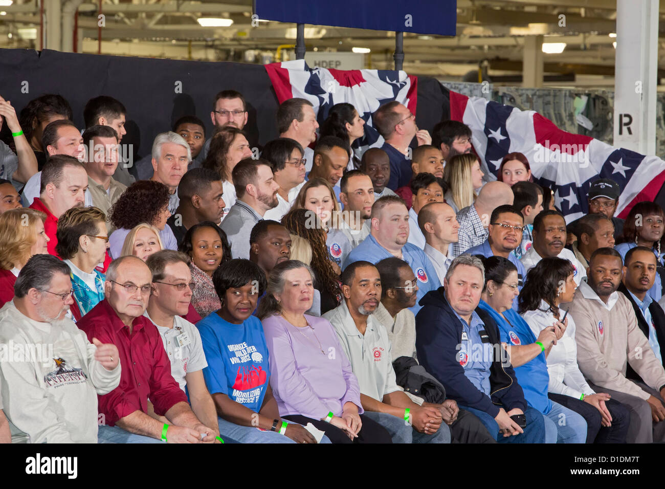 A crowd of auto workers and other guests waits to hear President Barack Obama speak at a Detroit Diesel factory. - Stock Image