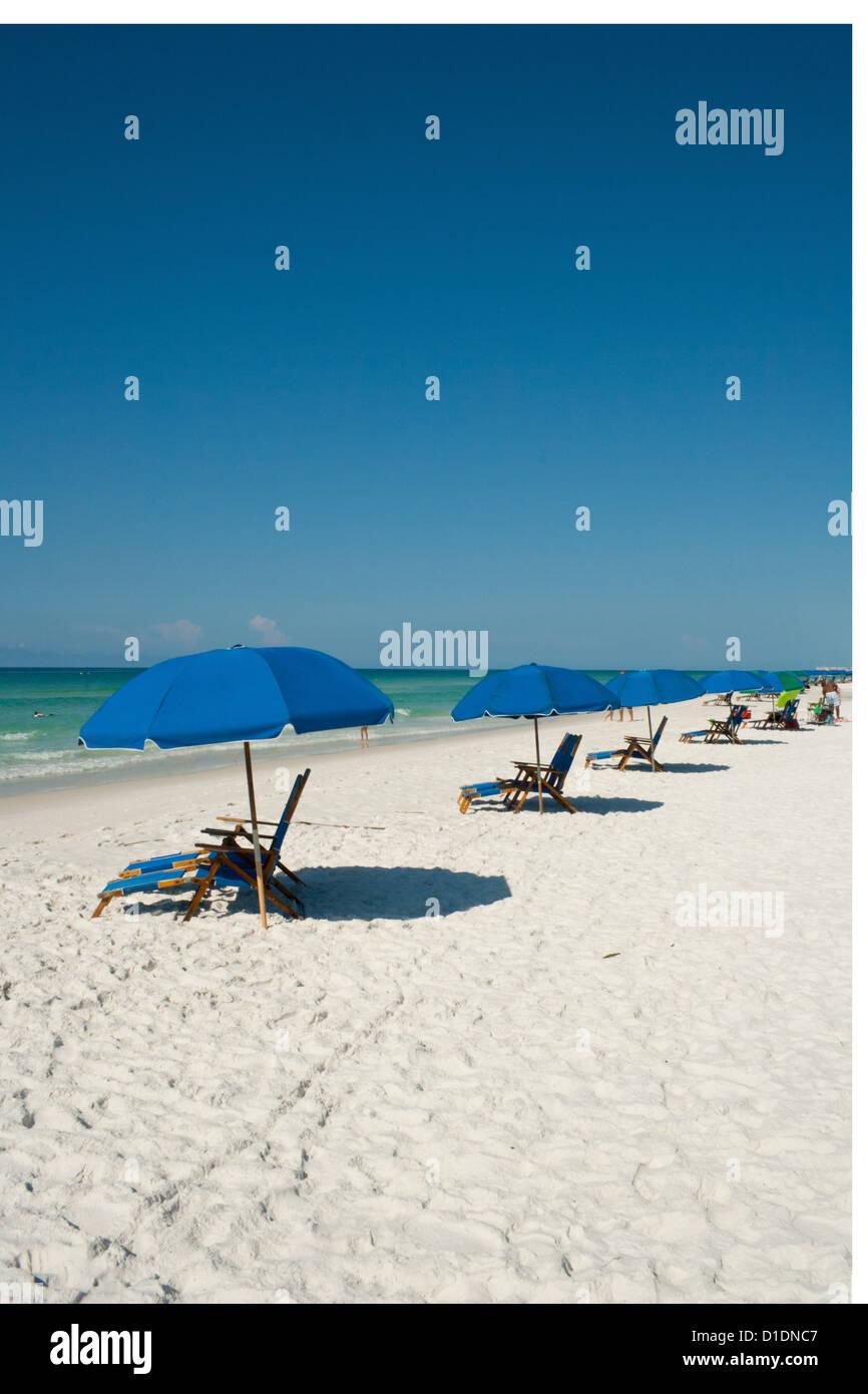 Blue umbrellas along the beach - Stock Image
