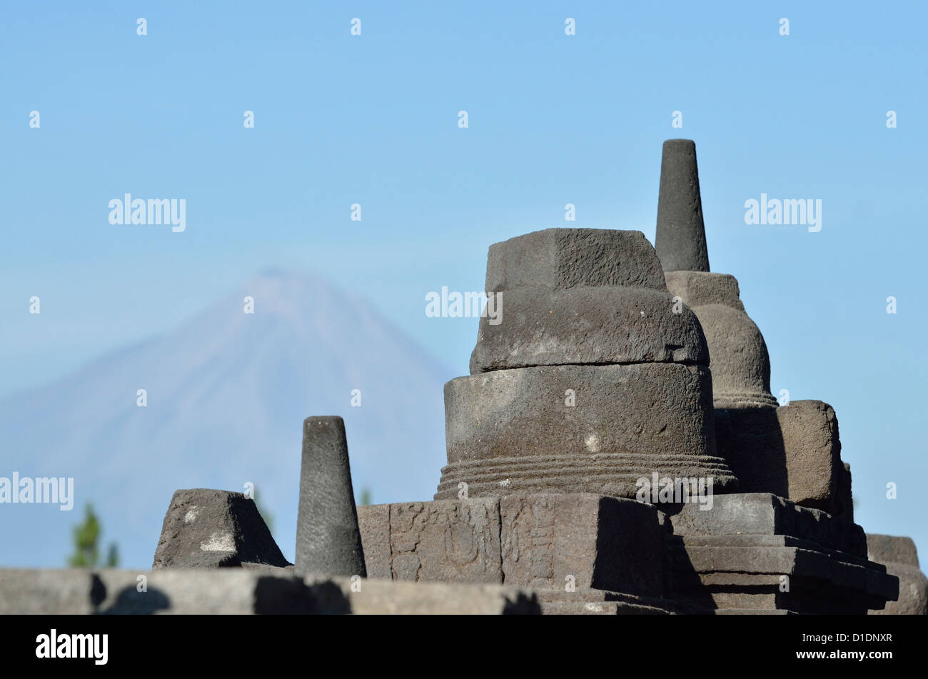Some decorative parts of the buddhist' monastery of Borobudur, with mount Merapi as a backdrop; Borobudur; Central - Stock Image