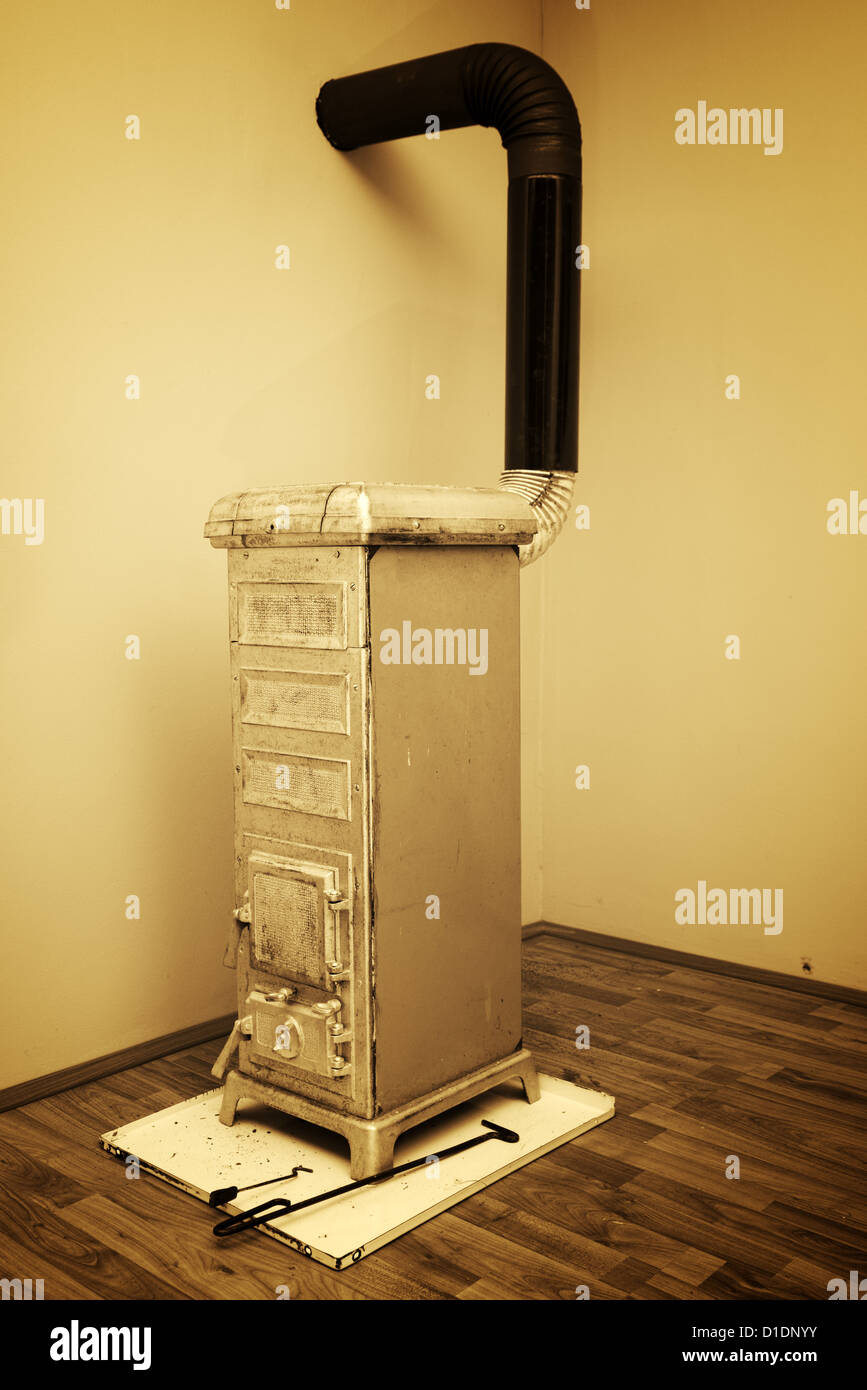 Old stove in the corner of the room - Stock Image