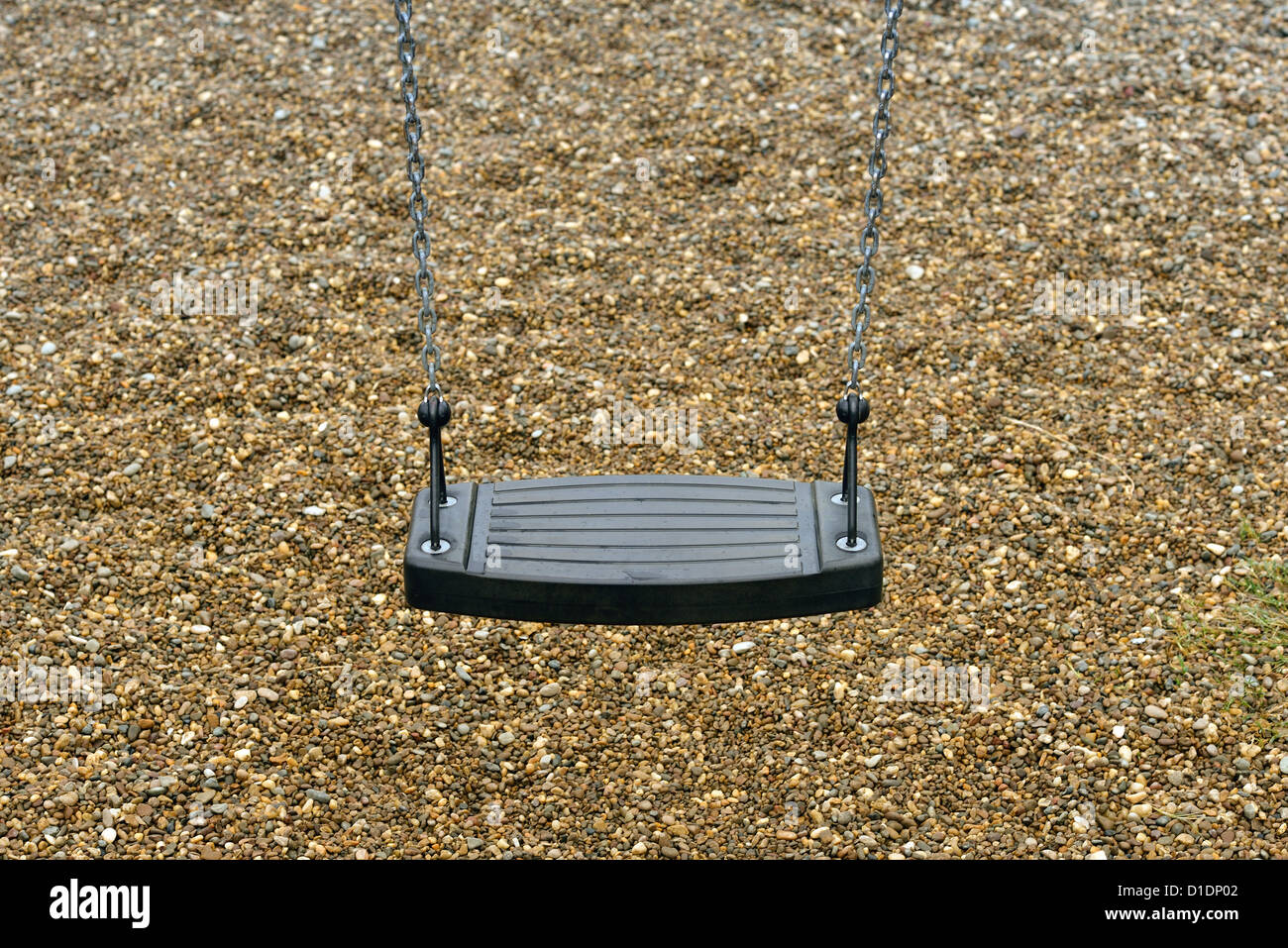 Empty playground swing in a empty park. - Stock Image