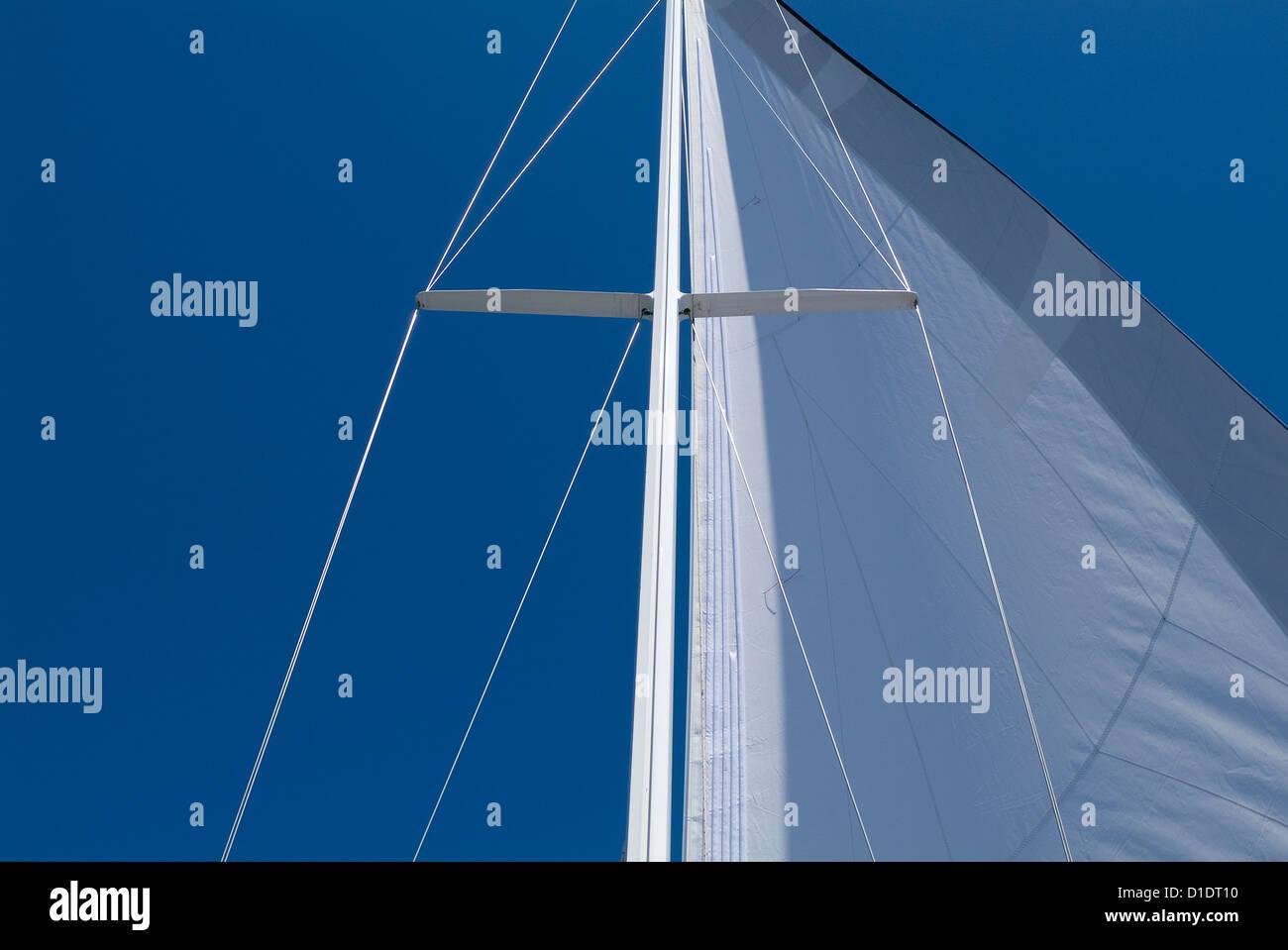 Sailboat mast mainsail, lower shroud, cap shroud and spreader. - Stock Image
