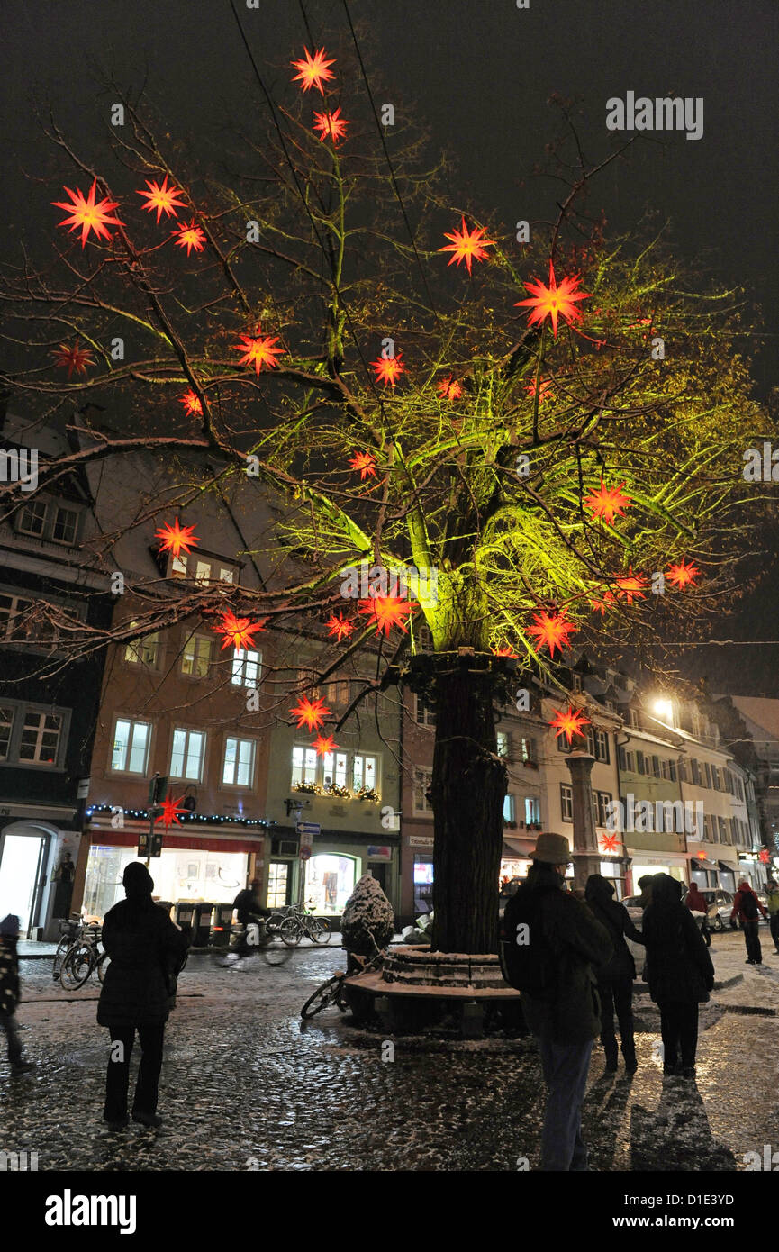 Passers-by admire a tree decorated with Christmas stars in Freiburg, Germany, 11 December 2012. Photo: Patrick Seeger - Stock Image