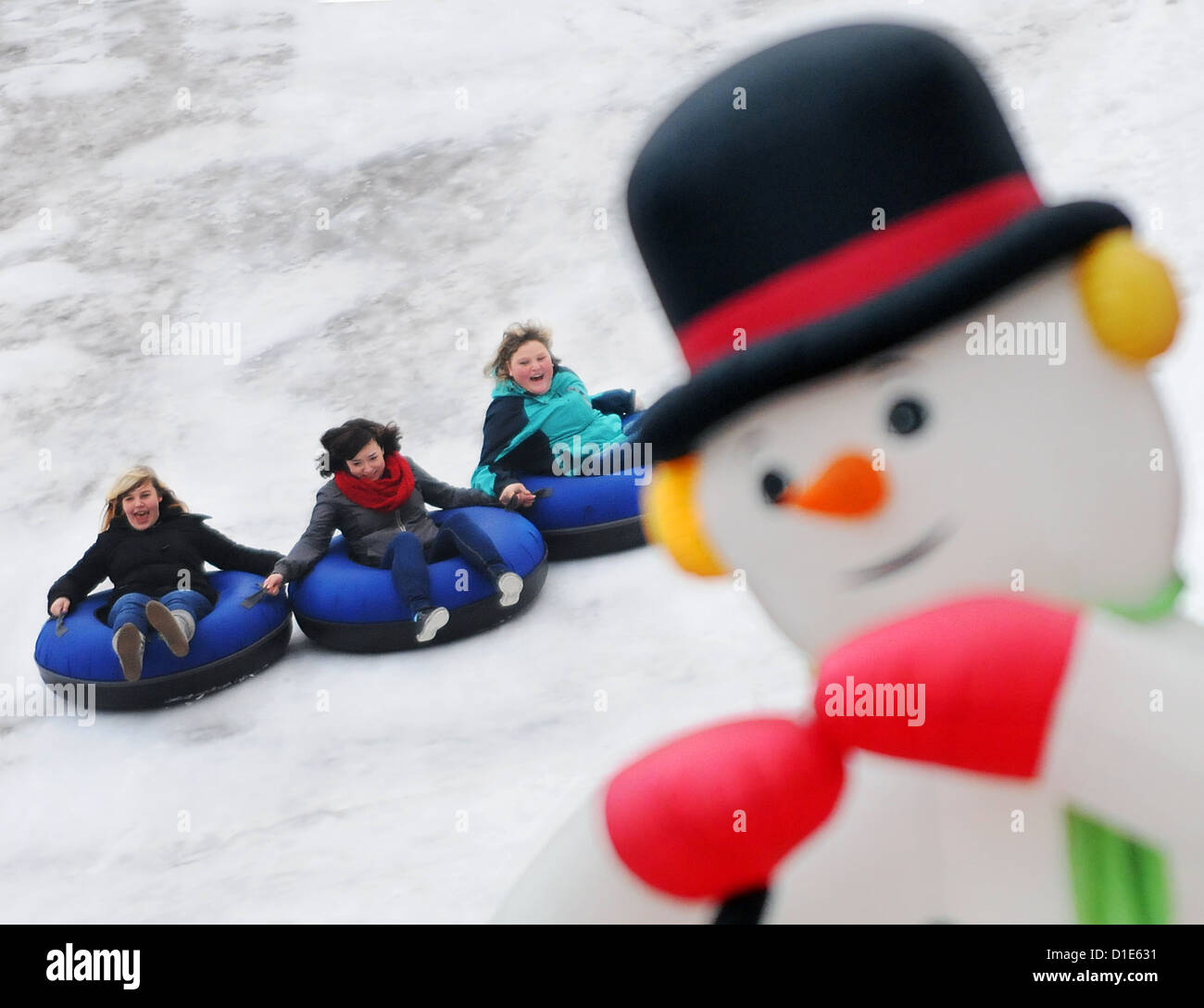Chrissy, Caro and Ari (l-r) toboggan in giant hoops at the artificial snow hill on Potsdamer Platz in Berlin, Germany, - Stock Image