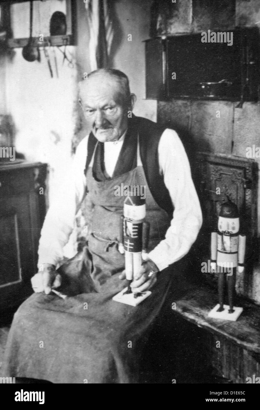 An undated historical photograph shows Wilhelm Fürster with two wooden nutcrackers in his workshop in Seiffen - Stock Image