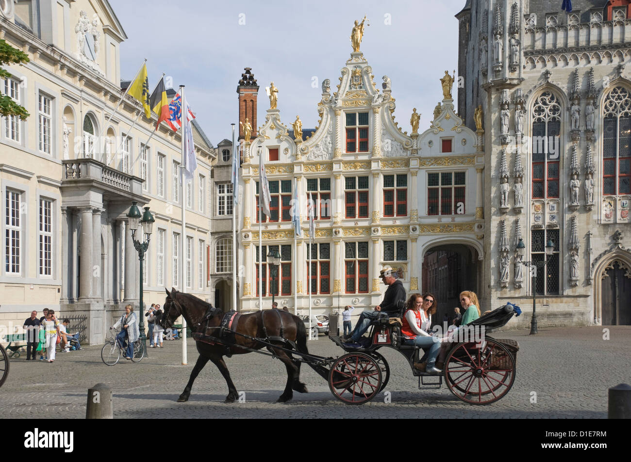 A horse drawn carriage crosses the Burg Square, passing the Stadhuis (Town Hall) buildings, Brugge, Belgium, Europe - Stock Image