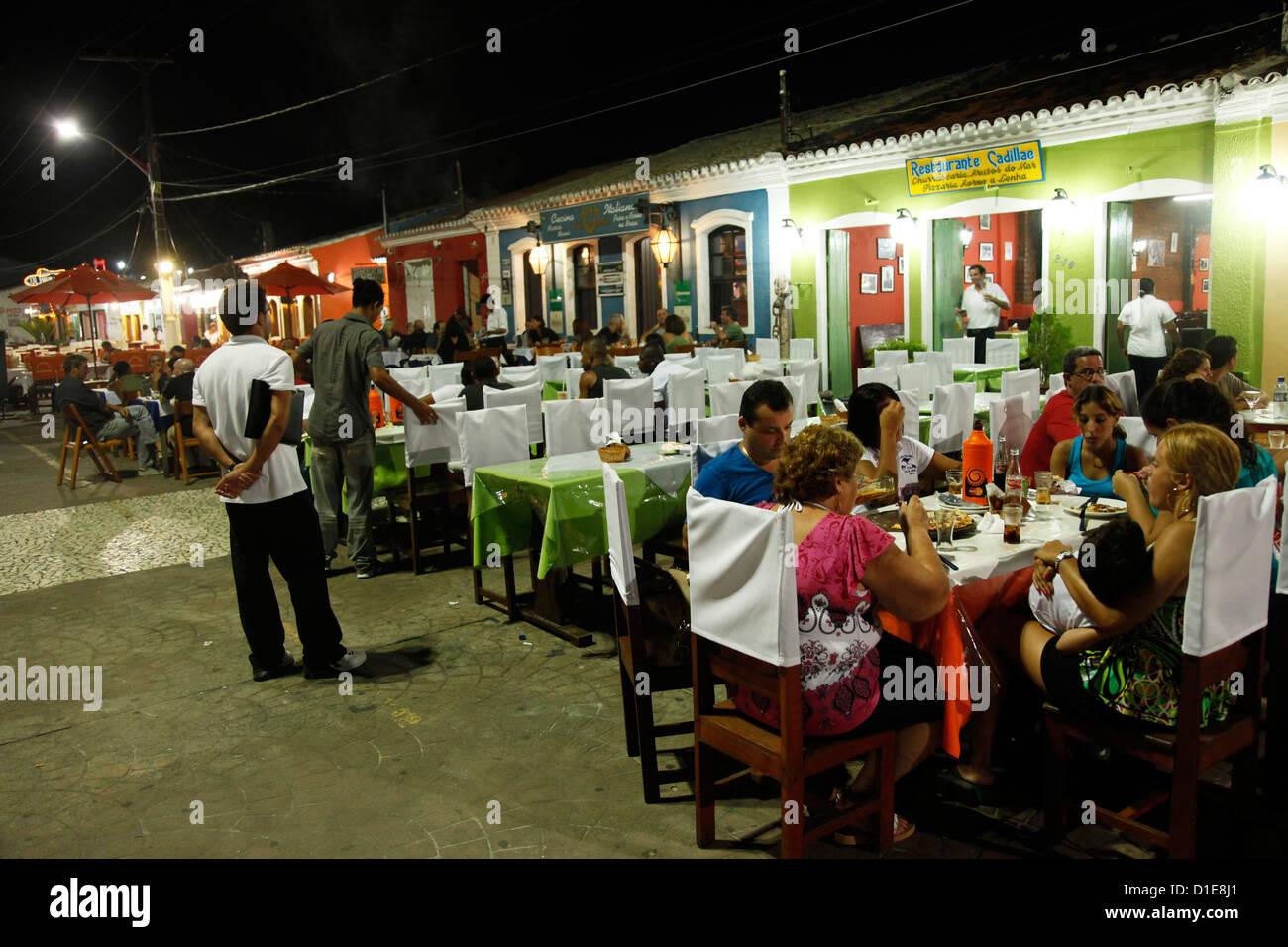 People sitting at outdoor restaurants in Porto Seguro, Bahia, Brazil, South America - Stock Image