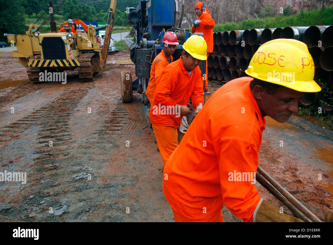 Workers putting pipes for natural gas near Congonhas, Minas Gerais, Brazil, South America - Stock Image