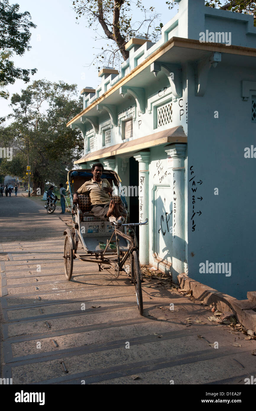 Cycle rickshaw wallah waiting for fare next to a riverside shrine, Hooghly River, Serampore, West Bengal, India - Stock Image