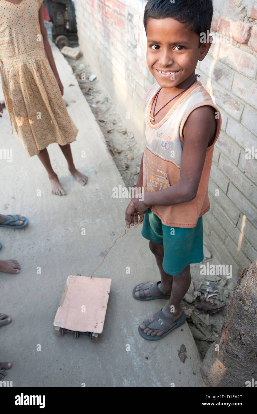 Young smiling village boy with wheeled toy vehicle pulled on piece of wire, in a village street, rural West Bengal, - Stock Image
