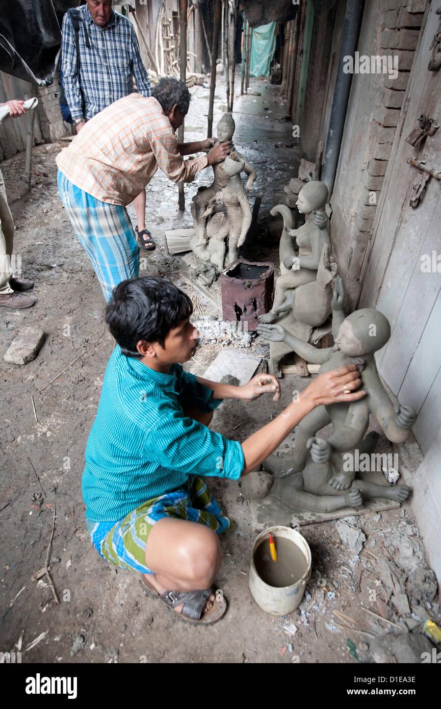 Sculptors making models from clay from the River Hugli, Kumartuli district, Kolkata, West Bengal, India - Stock Image