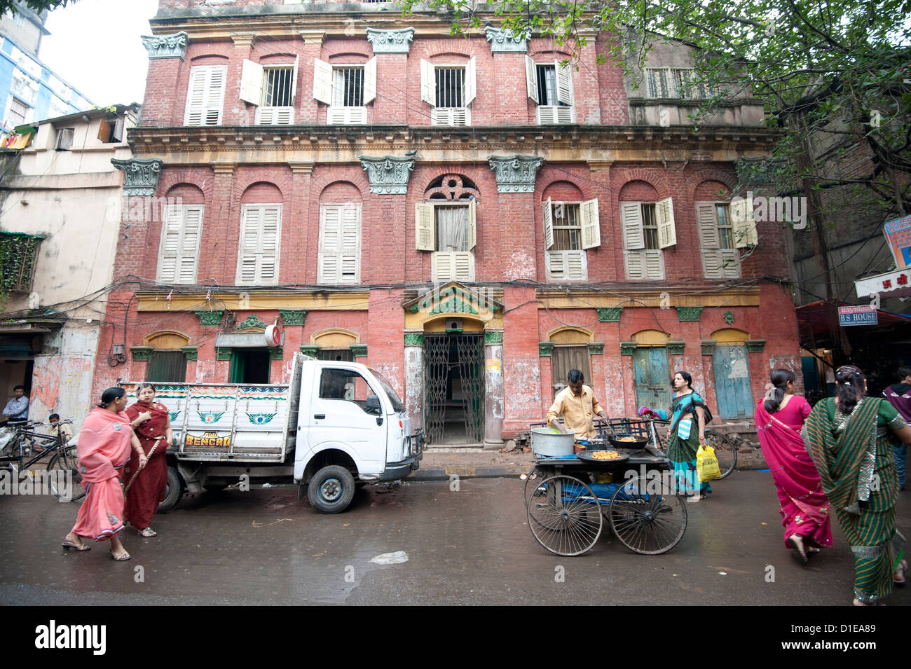 Street snack seller with his wheeled stall outside beautiful old Raj era building in Kolkata back street, West Bengal, - Stock Image