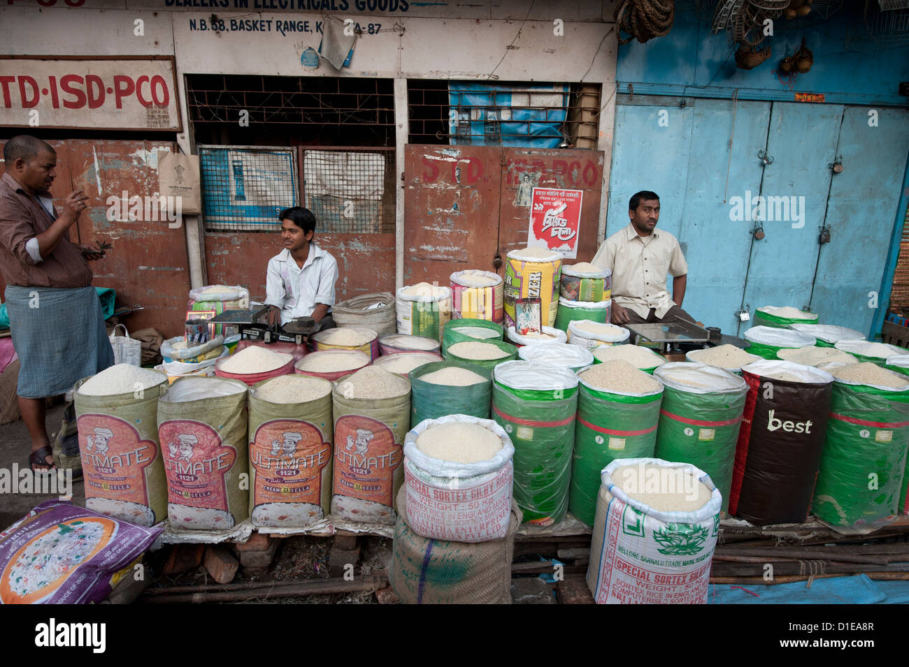 Rice wallahs sitting behind sacks of rice waiting for customers in the early morning, New Market, Kolkata, West - Stock Image