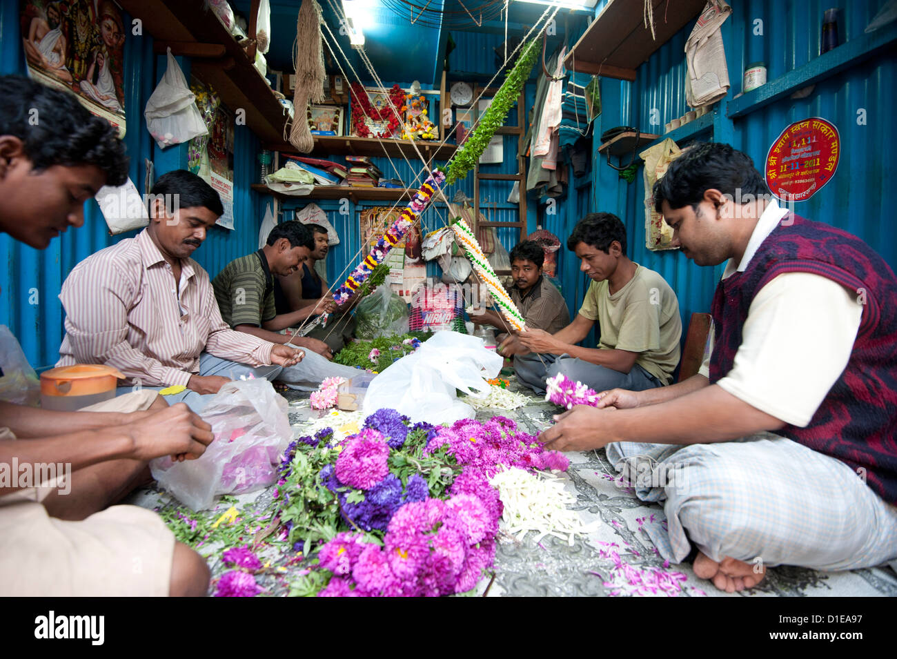 Mala makers (garland makers) at work in Kolkata's morning flower market, Howrah, Kolkata, West Bengal, India, - Stock Image