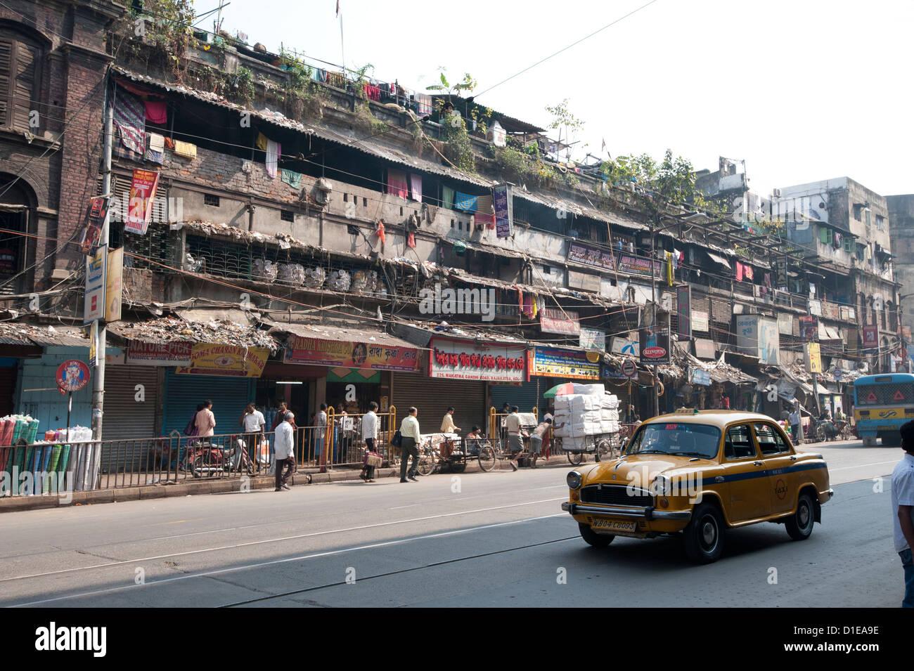 Yellow Kolkata taxi passing Kolkata slums in the early morning, Kolkata, West Bengal, India, Asia - Stock Image