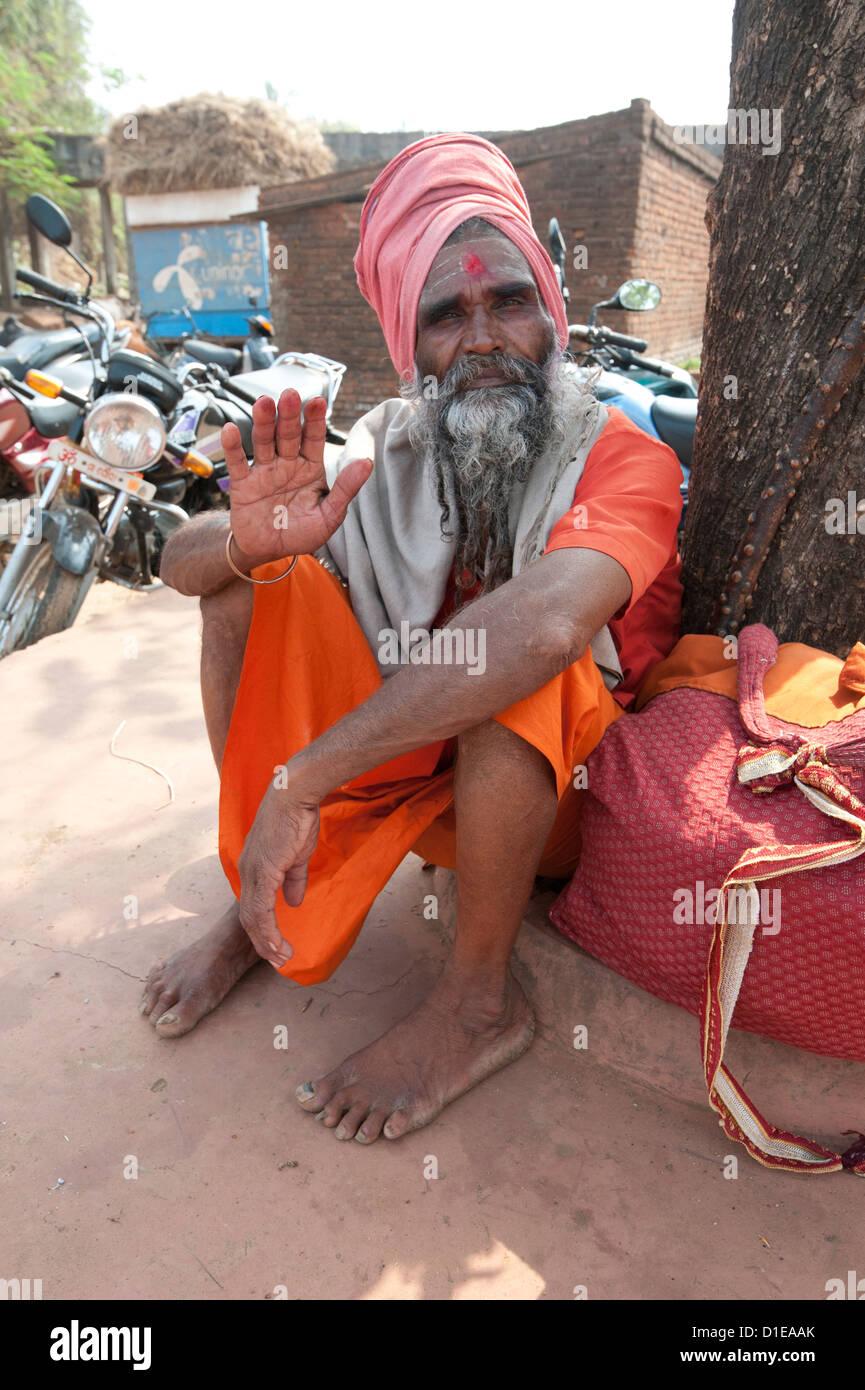 Travelling saddhu dressed in holy colour orange, resting beneath a village tree, Bhubaneshwar, Orissa, India, Asia - Stock Image