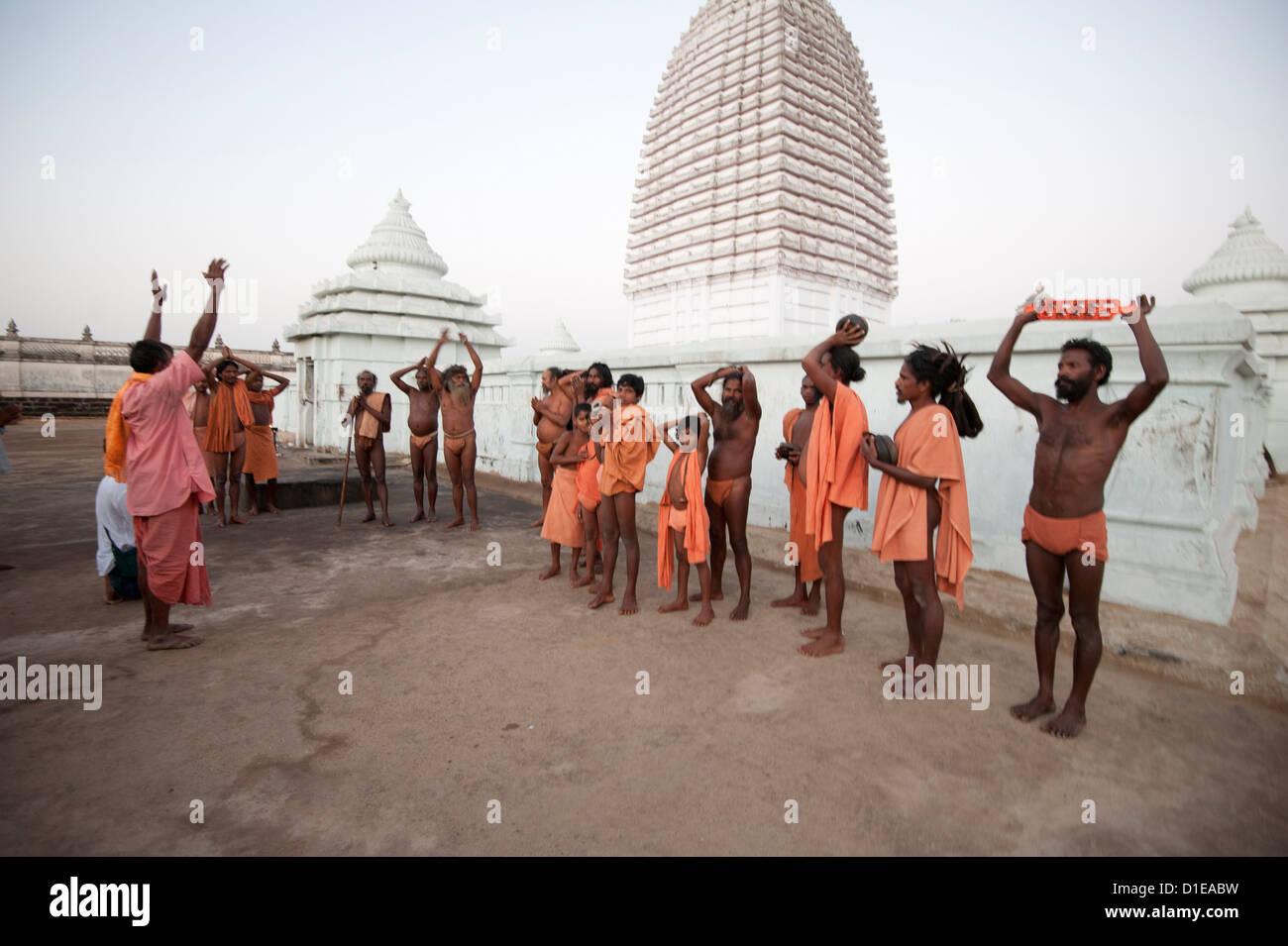 Joranda monks in ritual prayer at dusk at temple containing dhuni, eternal butter lamp, Joranda, Dhenkanal, Orissa, - Stock Image