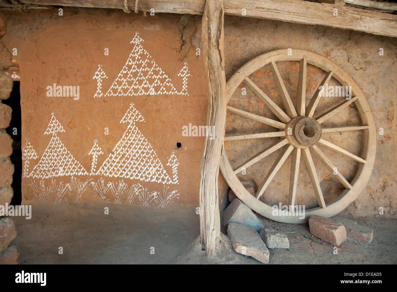 Village house wall with typical Orissa rice flour painting, and wooden cartwheel, Naupatana weaving village, rural - Stock Image