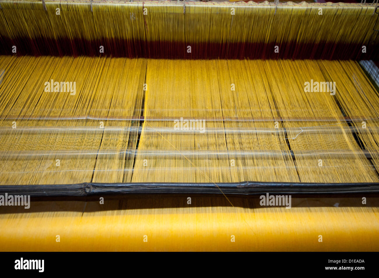 Yellow dyed silk being woven on loom, Naupatana weaving village, rural Orissa, India, Asia - Stock Image