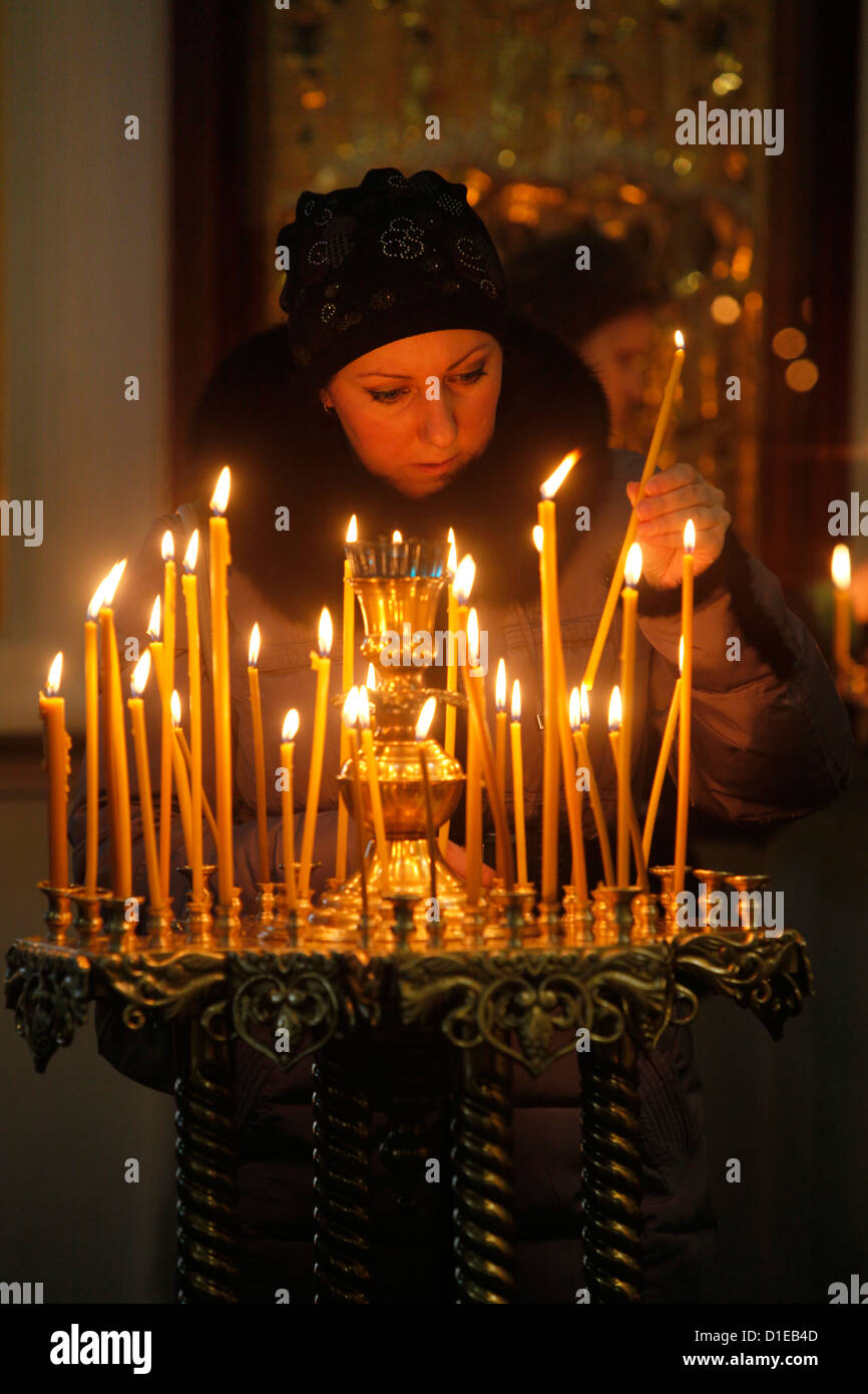 Woman lighting a candle, Trinity Cathedral, St. Petersburg, Russia, Europe - Stock Image