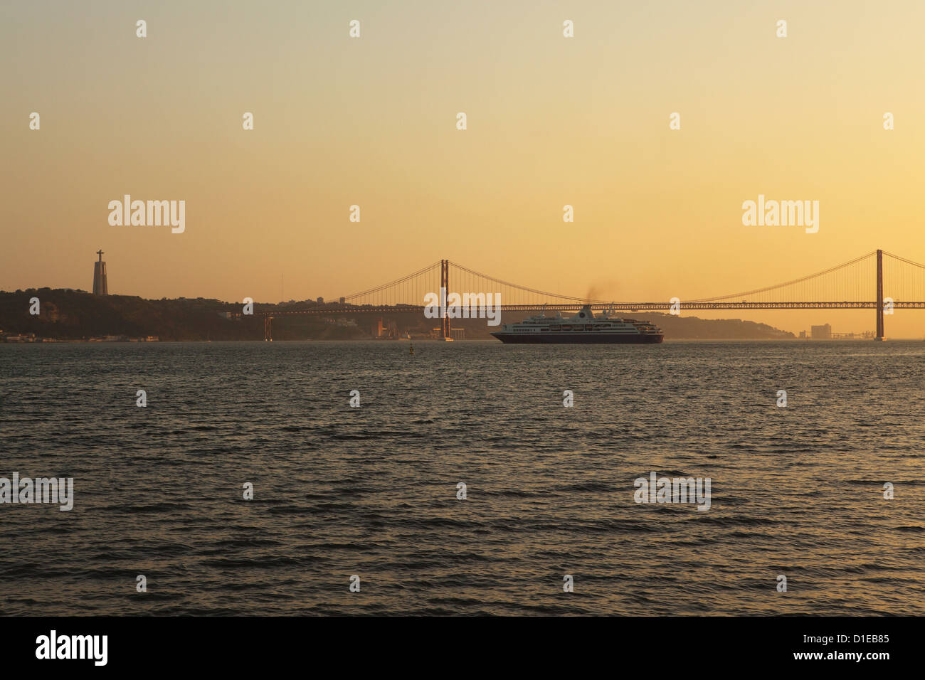 A cruise liner turns into the sunset, on the River Tagus under the 25 April Bridge and Christus Rei statue, Lisbon, - Stock Image