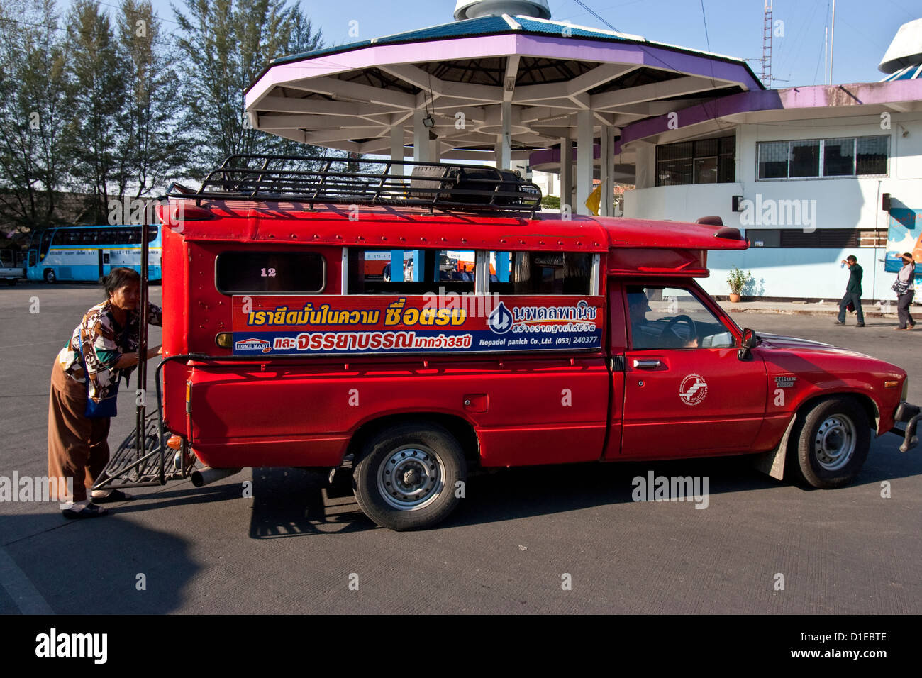 Traditional Red Songthaew Taxi, Chiang Mai Bus Station, Thailand - Stock Image