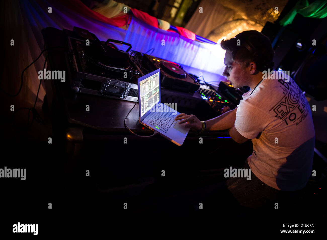 A DJ lining up music on his laptop computer to play at a dance party rave disco club night , UK - Stock Image