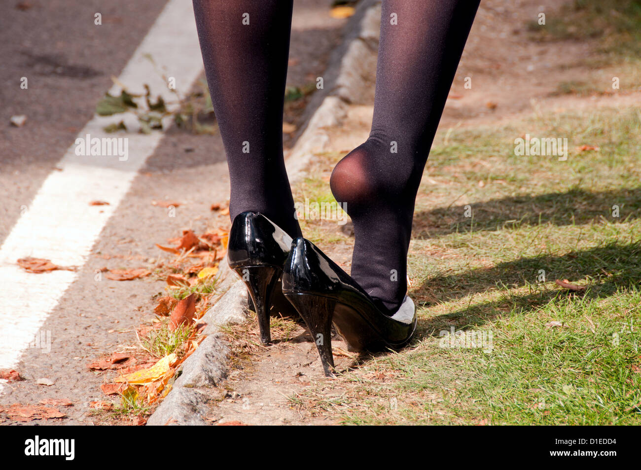 A woman stretching her legs and feet whilst wearing shiny black shoes and stockings - Stock Image