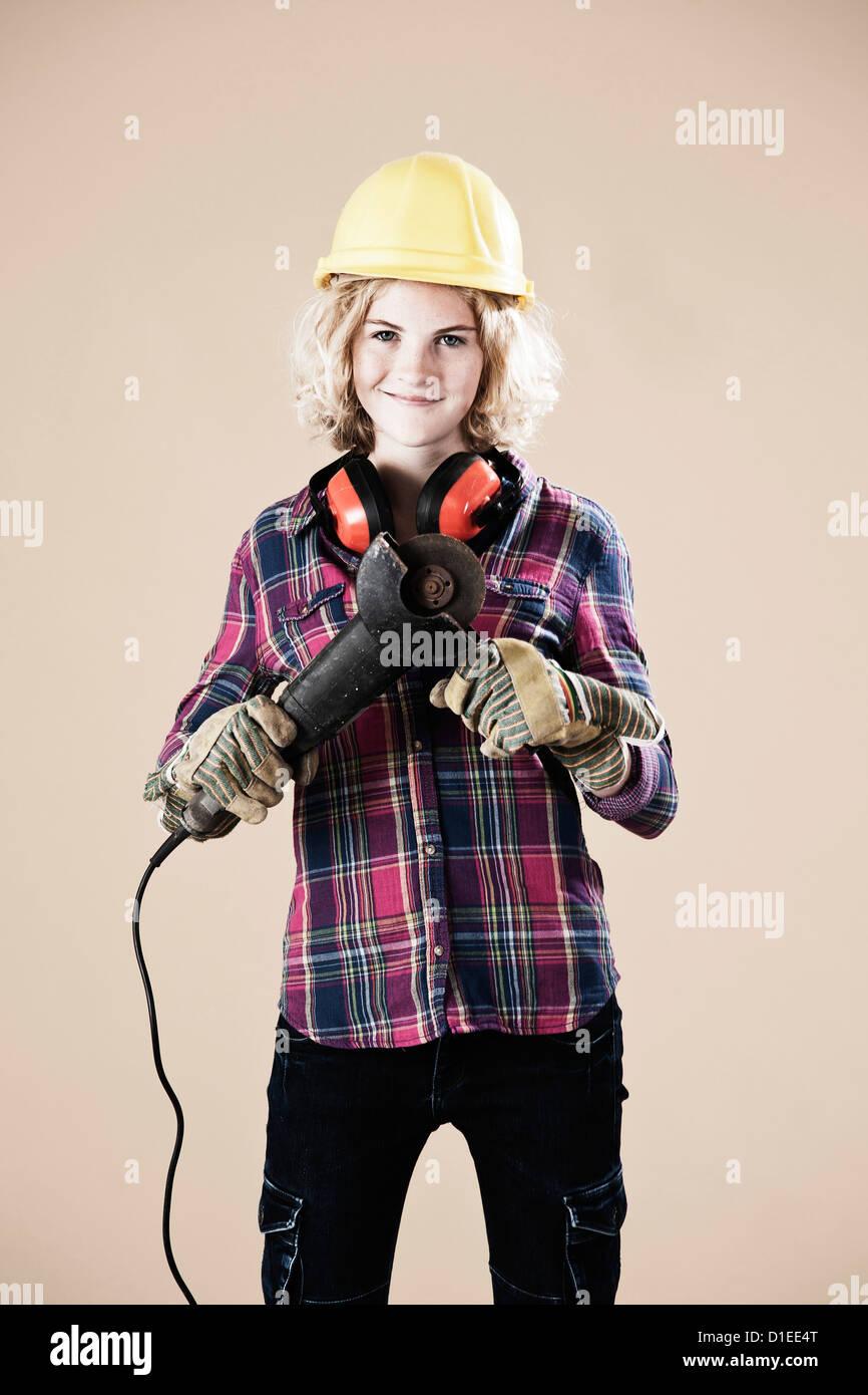 Teenage girl with hard helm and angle grinder - Stock Image