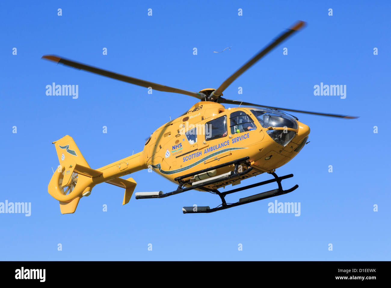 Yellow Scottish Air Ambulance Service Helicopter flying overhead with a casualty from a rescue mission. Sutherland - Stock Image