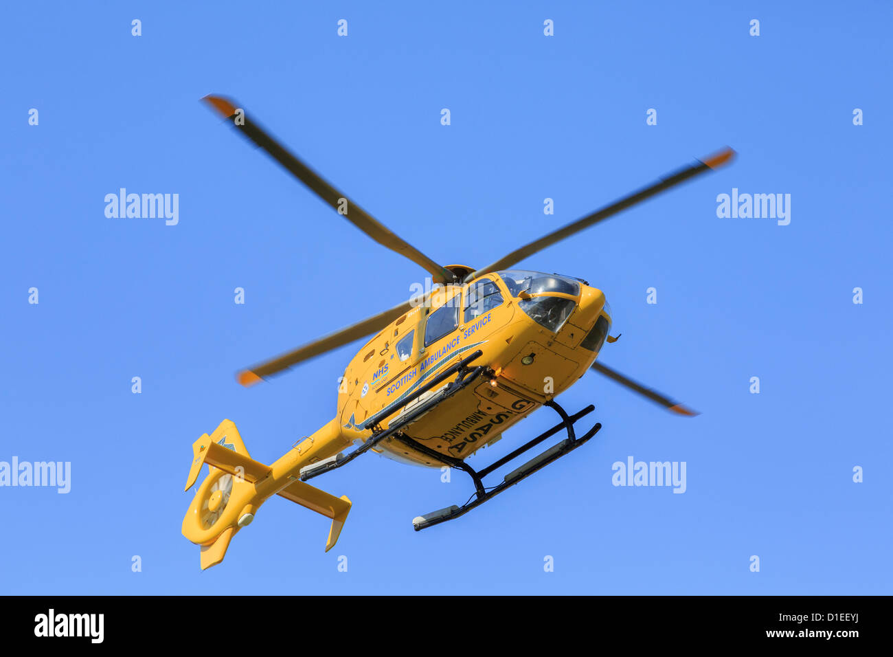 Yellow Scottish Air Ambulance Service Helicopter flying overhead from a rescue mission seen from below against a Stock Photo