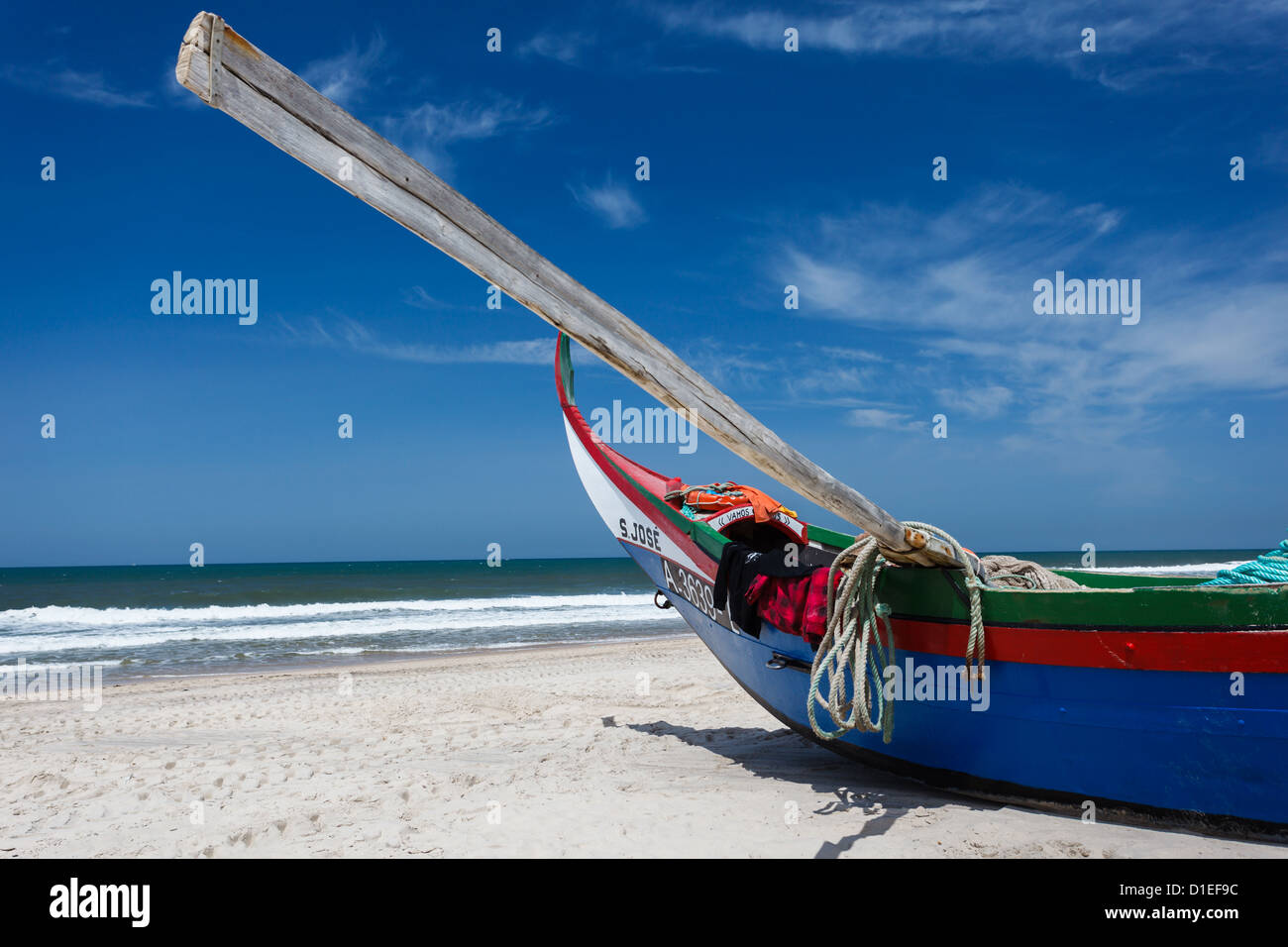 Prow of colorful blue Portuguese moliceiros fishing boat with oar lifting skyward sits on beach at ocean in the - Stock Image