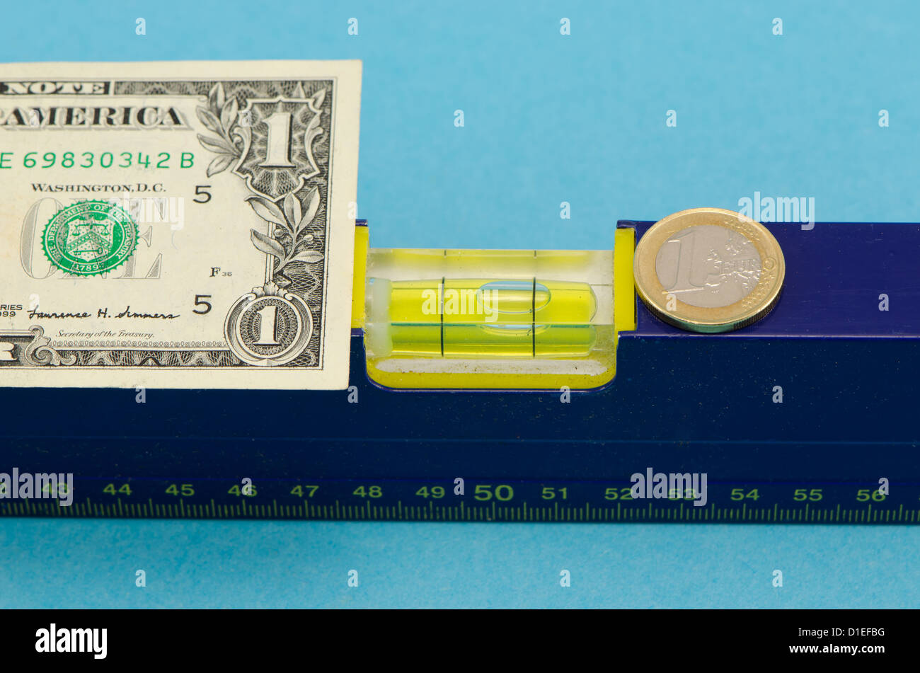spirit level tool and usd dollar banknote and euro coin on blue background. - Stock Image