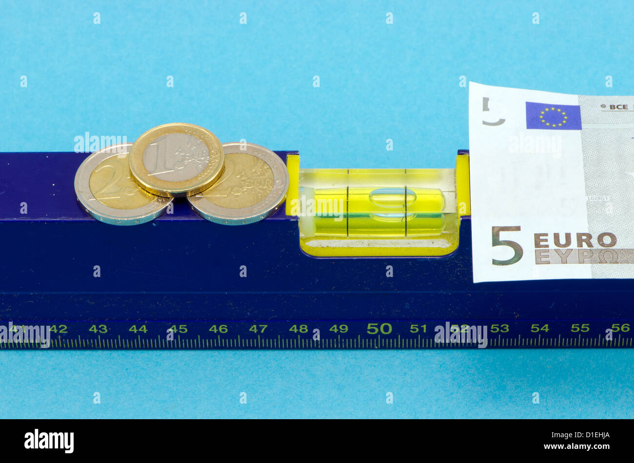 spirit level tool euro banknote and coins on blue background. - Stock Image