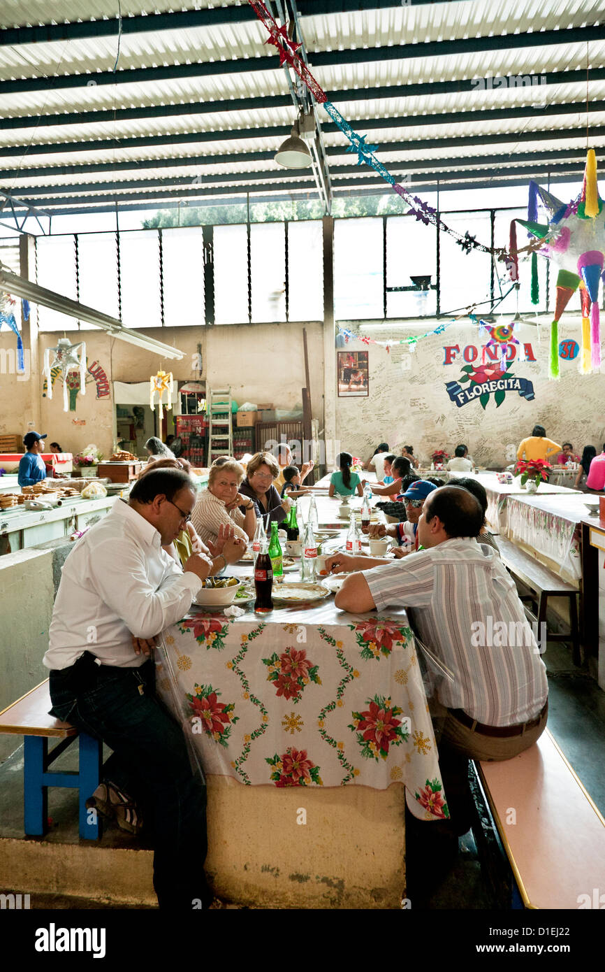 festive scene as Mexican families sit at long tables for Saturday comida meal at Christmas decorated restaurant - Stock Image