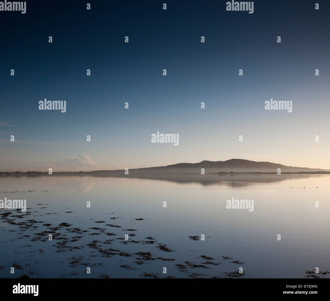 Howth, Co. Dublin in sunshine at dawn from Clontarf waterfront - Stock Image