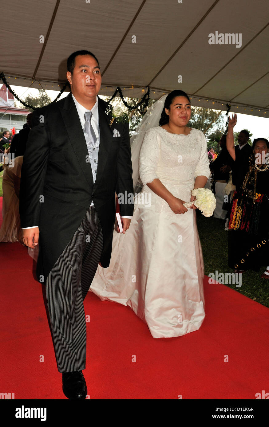 The Crown Prince of Tonga and his bride, Princess Sinaitakala ,walk up the red carpet as they arrive at their Wedding - Stock Image
