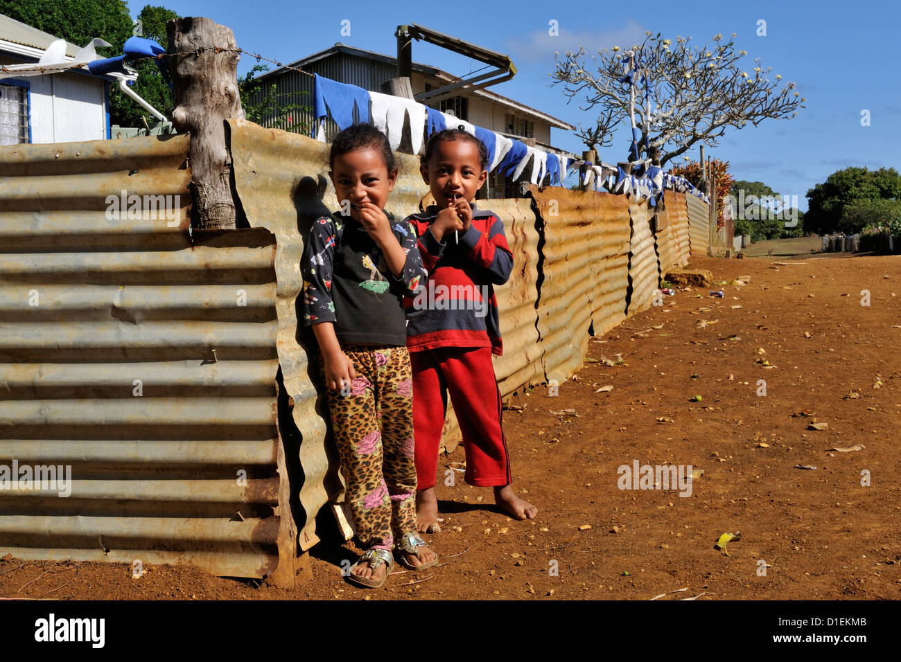 Two children standing by fencing lining the main street through the village on the island of O'ua in the southern - Stock Image