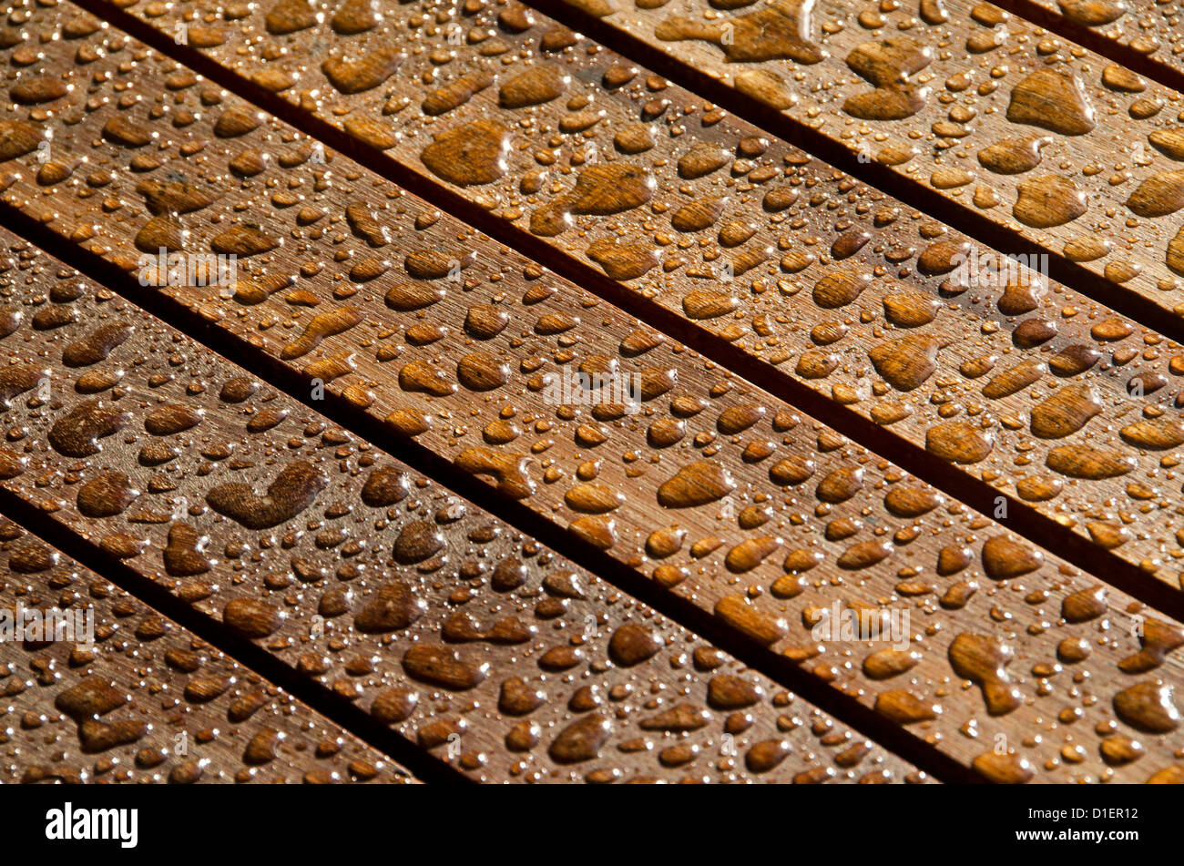 Rain drops on teakwood - Stock Image