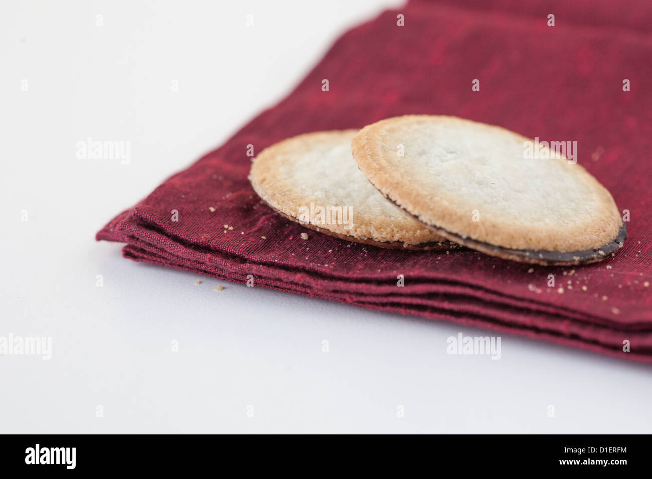 two cookies sit on maroon napkin - Stock Image